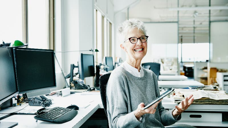 An older businesswoman sits smiling in an office
