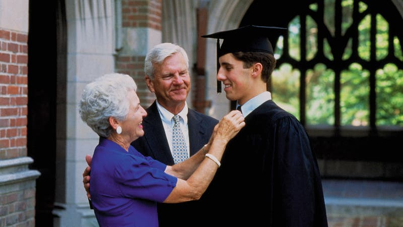 Two grandparents congratulate a young college graduate