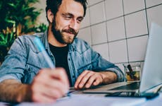 Bearded man happily working on laptop in cafe