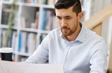 A man looks concerned as he stares at a sheet of paper.
