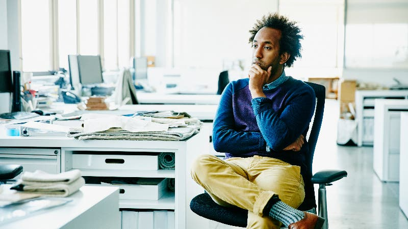 An African-American man sits a work desk with a thoughtful look