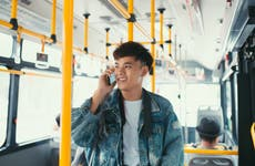 Man talking on phone while riding city bus.