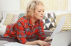 Woman lying on bed looking at finances.