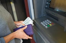 A woman gets cash out of an ATM.