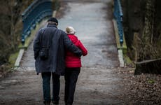 An older couple walks toward a bridge