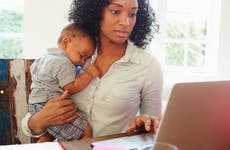 Young mother working on laptop while holding sleeping baby