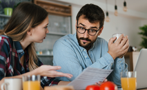 couple at kitchen table holding bills