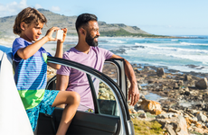 Man and boy look at beach while standing by car