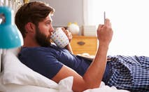 A man sits in bed, looking at his phone.
