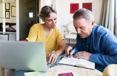 An older white couple examines their finances by the computer