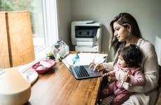 Mother multi-tasking with infant daughter in home office