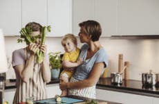 A lesbian couple has fun in the kitchen playing with their child.