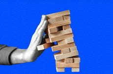 Hand balances a falling Jenga tower