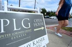 Woman walks past an open house sign.