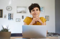A woman sits at her laptop computer and stares into the distance