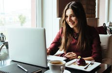 young woman with coffee working on open laptop