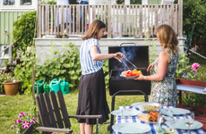 mother and daughter grilling in backyard of home