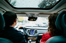 man and woman driving in car on rainy day