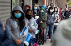 Citizens wearing protective masks form lines to receive free food from a food pantry in Brooklyn, New York