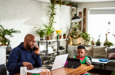 Father on phone call and working with son watching tablet