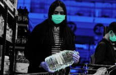 Consumer grabbing water bottle with mask during coronavirus