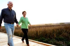 Older white couple walks down boardwalk