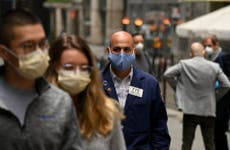 A trader walks in front of the New York Stock Exchange during the coronavirus pandemic