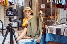Young woman showing clothes to camera.