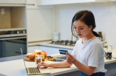 Woman sitting in her kitchen looking at credit card