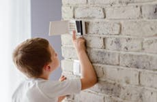 A boy reaching up to activate a home security system keypad.