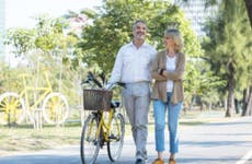 A senior couple walking together on a sunny day. The man is pushing a bicycle with a basket on it.