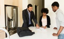 Couple talking to broker in new house