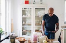 elderly man checking shopping list in kitchen at home