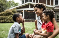 African American single mother sitting with her two kids in the front yard of their home.