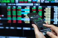 A trader looks at his phone for bond prices