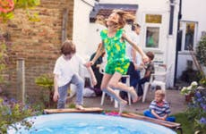 A young girl leaping into a pool in a back garden with friends and family in the background.