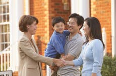 A young Asian couple and a child sign a real estate deal