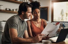 Interracial couple white man and black woman sitting together at a table reviewing their finances.