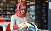 Woman studies in college library.