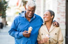 An older African-American couple walks together with ice cream cones