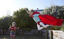 Two boys play superheroes out in the backyard.
