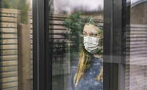 A woman wearing a facemask stares out the window.