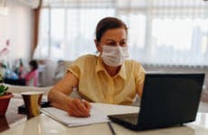 A woman wearing a facemask reviews her online information and accounts.