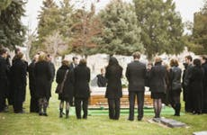 A group of people dressed up and standing around a coffin at a burial.