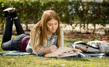 Student studying on grass on college campus.