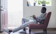 A young black man lounges about in his condo while on the phone.
