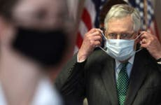 Senate Majority Leader Mitch McConnell puts on a mask