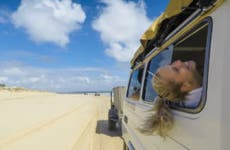 A woman sticks her head out the window of a jeep and enjoys the breeze during a road trip.