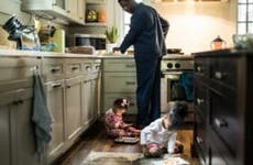 A father makes breakfast for his two young children at home.