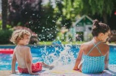 Two children splash by the pool.